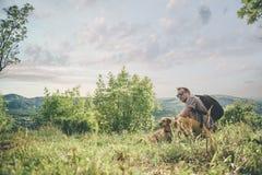 Homme avec un chien se reposant sur le pré photographie stock
