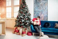 Homme avec un durnig de cadeau les vacances d'hiver à la maison image stock
