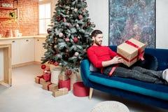 Homme avec un durnig de cadeau les vacances d'hiver à la maison photographie stock libre de droits