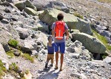 Homme avec un fils en montagnes Images libres de droits