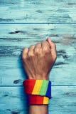 Homme avec un foulard arc-en-ciel-modelé dans son poignet Image stock