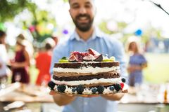 Homme avec un gâteau sur une célébration de famille ou une réception en plein air dehors photographie stock libre de droits