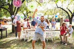 Homme avec un gâteau sur une célébration de famille ou une réception en plein air dehors images stock
