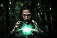 Homme avec un globe rougeoyant mystérieux Photographie stock libre de droits
