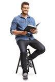 Homme avec un livre se reposant sur une chaise Image libre de droits