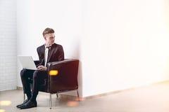 Homme avec un ordinateur portable dans un bureau blanc Photo libre de droits