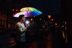Homme avec un parapluie d'arc-en-ciel la nuit sur la rue Harmonie, yeux fermés Lumières de la ville de nuit images libres de droits
