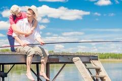 Homme avec un poteau de pêche et sa femme aimée sur un pilier en bois o Image libre de droits