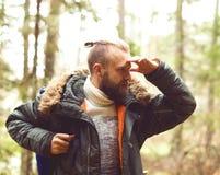 Homme avec un sac à dos et une barbe augmentant dans une forêt Photos stock