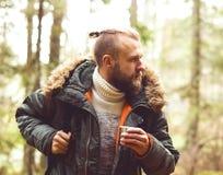 Homme avec un sac à dos et une barbe augmentant dans une forêt Photos libres de droits