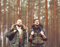 Homme avec un sac à dos et une barbe et son ami dans la forêt Photos stock