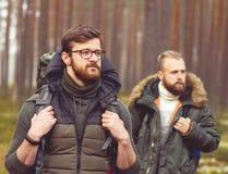 Homme avec un sac à dos et une barbe et son ami dans la forêt Photo libre de droits