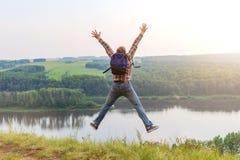 Homme avec un sac à dos sautant sur une colline Photos libres de droits