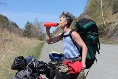 Homme avec un sac à dos se reposant sur une bicyclette et une eau potable  Image libre de droits