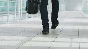 Homme avec un sac à main marchant dans un terminal d'aéroport moderne banque de vidéos