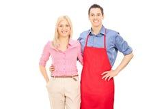 Homme avec un tablier rouge posant avec son amie blonde Images stock