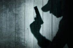 Homme avec une arme à feu dans l'ombre sur un fond en bois Photographie stock