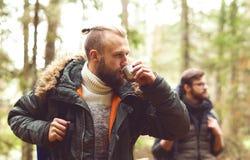 Homme avec une barbe et son ami trimardant dans une forêt Photos libres de droits