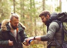 Homme avec une barbe et son ami trimardant dans une forêt Photographie stock