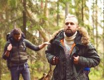 Homme avec une barbe et son ami trimardant dans une forêt Image libre de droits