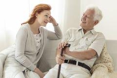 Homme avec une canne parlant à sa fille et sourire images stock
