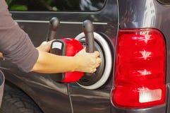 Homme avec une machine d'amortisseur de puissance nettoyant la pièce arrière d'une voiture Image stock