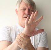 Homme avec une main endolorie Photos stock