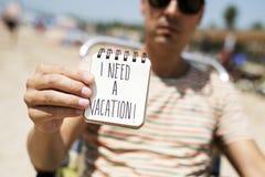 Homme avec une note avec le texte j'ai besoin des vacances Photographie stock libre de droits