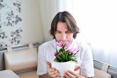 Homme avec une orchidée rose dans la chambre Image stock