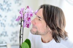 Homme avec une orchidée rose dans la chambre Images libres de droits