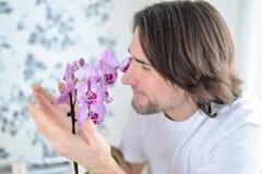 Homme avec une orchidée rose dans la chambre Image libre de droits