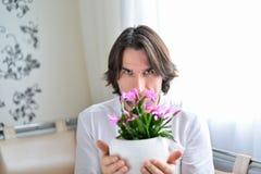 Homme avec une orchidée rose dans la chambre Photo stock