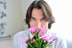 Homme avec une orchidée rose dans la chambre Photos libres de droits