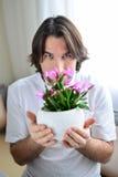 Homme avec une orchidée rose dans la chambre Photos stock