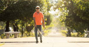Homme aveugle traversant la rue et marchant avec la canne Photographie stock libre de droits