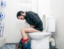 Homme ayant des problèmes dans la toilette Images stock
