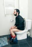 Homme ayant des problèmes dans la toilette Photos stock