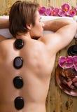 Homme ayant le massage en pierre dans le salon de station thermale Photo libre de droits