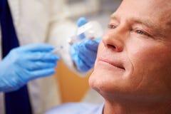 Homme ayant le traitement de Botox à la clinique de beauté images stock