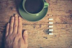 Homme ayant les pilules et le café Image libre de droits