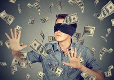 Homme bandé les yeux essayant d'attraper des billets de banque de billets d'un dollar volant en air Photographie stock libre de droits