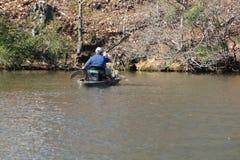 Homme barbotant dans son petit bateau photographie stock libre de droits
