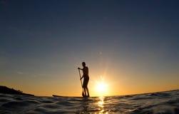 Homme barbotant son panneau de vague déferlante au coucher du soleil Photo libre de droits