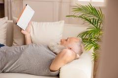 Homme barbu à l'aide du comprimé numérique et se trouvant sur le sofa à la maison Photographie stock