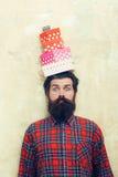 Homme barbu étonné jugeant les boîte-cadeau colorés empilés sur la tête image stock