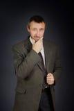 Homme barbu adulte dans le costume foncé sur le fond noir Photo stock