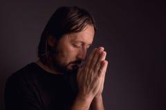 Homme barbu adulte priant dans la chambre noire Photo stock