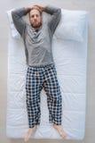 Homme barbu agréable se trouvant sur le lit photo libre de droits