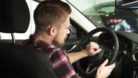 Homme barbu attirant souriant à l'appareil-photo au-dessus de son épaule se reposant dans une nouvelle voiture banque de vidéos
