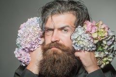 Homme barbu avec des fleurs d'hortensia image libre de droits